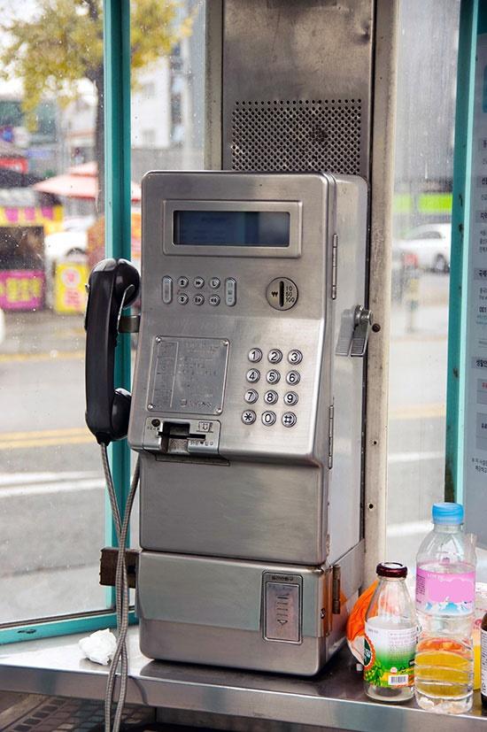 빈 물통과 음료병, 휴지 따위가 놓여 있는, 도시의 버스정류장 주변의 공중전화 부스 안 풍경은 퇴조하는 공중전화의 처지를 반영하고 있다.