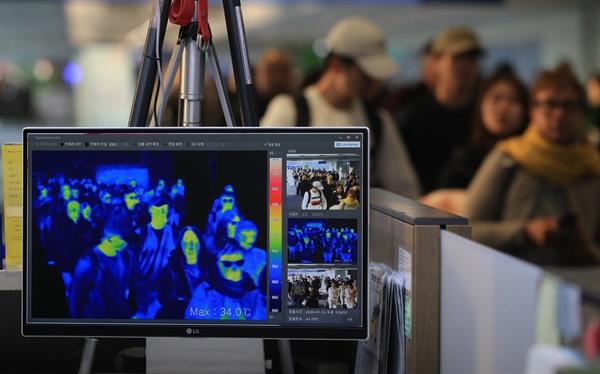 지난 23일 오후 인천국제공항 1터미널 입국장에서 질병관리본부 국립검역소 직원들이 열화상 카메라로 승객들의 체온을 측정하고 있다.