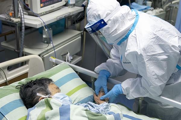 24일 중국 후베이성 우한대학 중난병원의 집중치료실에서 보호복을 입은 의료진이 신종 코로나바이러스 감염증 확진 환자를 돌보고 있다.