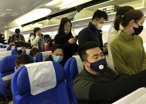 21일 중국 상하이를 출발해 우한으로 향하는 항공기에 탄 승객들이 신종 코로나바이러스 감염을 막고자 마스크를 쓰고 있다.