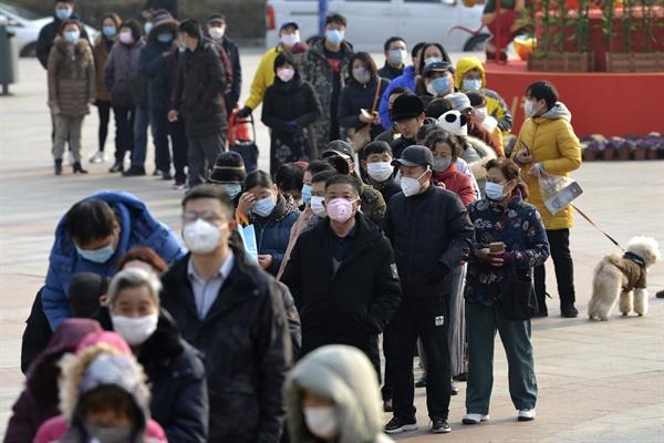 (난징 AP=연합뉴스) 신종 코로나바이러스 감염증이 확산 중인 가운데 29일 중국 장쑤성 난징의 한 약국에서 시민들이 마스크를 사기 위해 길게 줄을 서 있다.