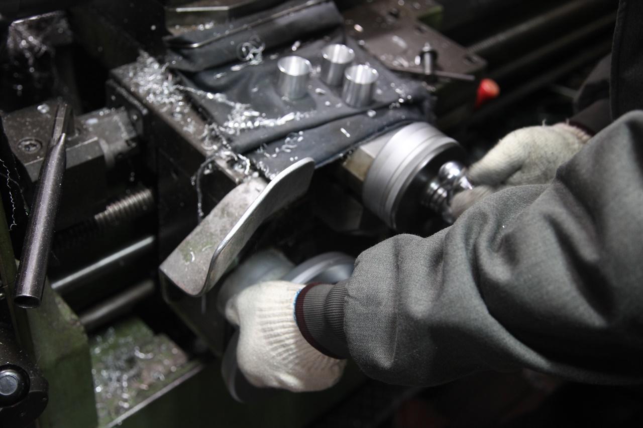선반기계로 금속을 정밀하게 가공 중인 기술자의 손.