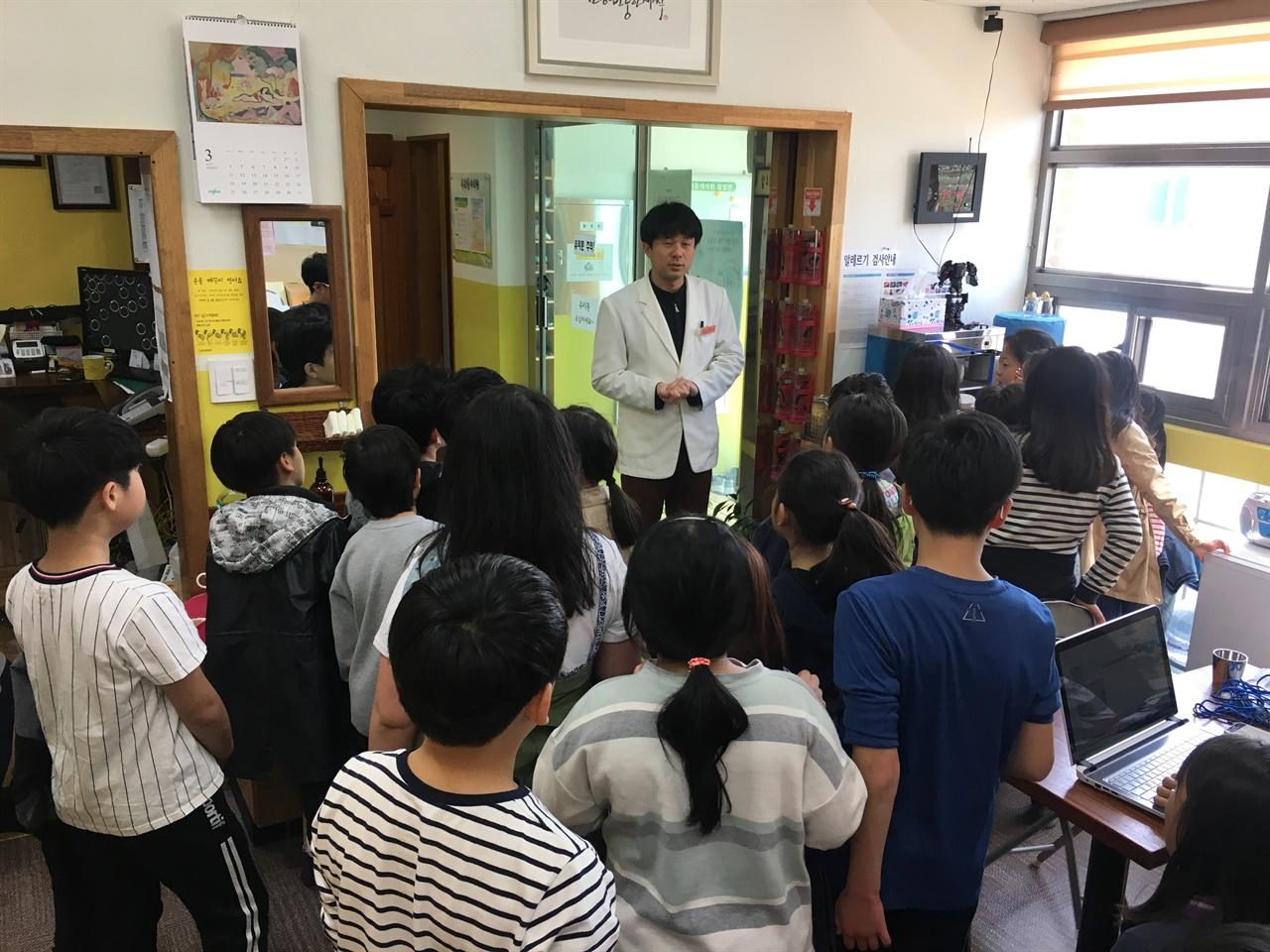의원에 찾아온 지역 학생들에게 우리동네의원을 소개하는 이훈호 원장  우리동네의원은 마을에 있는 학교에서 견학오기 좋은 장소다. 우리동네의원이 하는 일을 설명하는 것만으로 아이들은 의료와 복지, 사회적 가치, 협동조합에 대해 기본적인 이해를 할 수 있다.