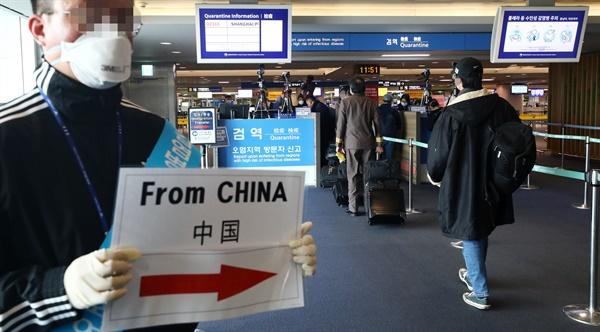 중국 상해발 입국자들이 28일 인천국제공항에서 건강상태 질문서를 작성한 뒤 이동하고 있다. 보건당국은 이날부터 신종 코로나바이러스 감염증 확산을 막고자 중국에서 들어오는 모든 입국자의 '건강상태 질문서' 제출을 의무화했다.