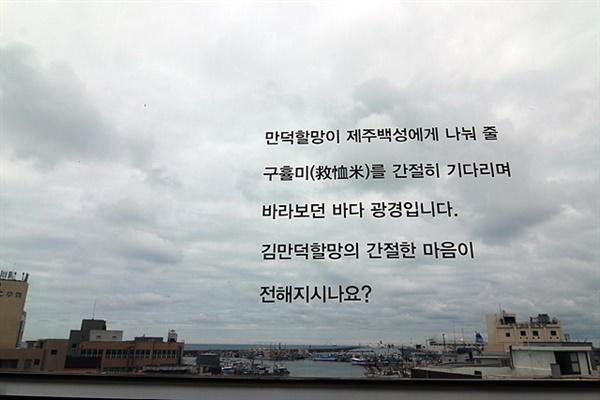 김만덕 기념관 유리창에 적힌 글로 김만덕이 제주민에게 나눠 줄 쌀이 오기를 기다리며 바다를 바라보던 간절한 마음을 생각해 보라는 글귀가 적혀있다.