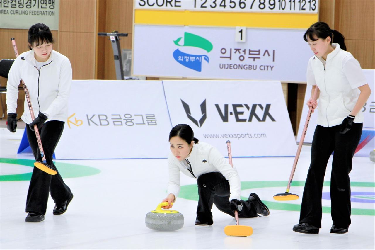 코리아 컬링 리그 경기에서 전북도청 정재이 선수(가운데)가 스톤을 투구하고 있다. 김지현(왼쪽), 신가영 선수가 스윕을 위해 달려가고 있다.