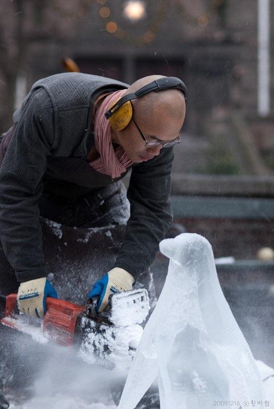 관객들 앞에서 얼음 펭귄 조각 작업을 하는 최병수 작가