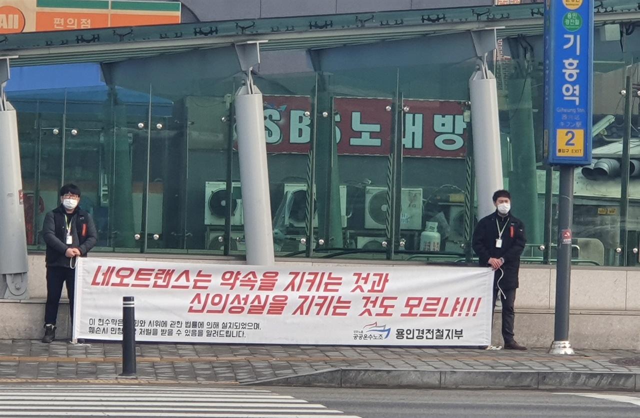 용인경전철 노조원들이 기흥역 앞에서 약식 현수막 시위를 벌이는 모습