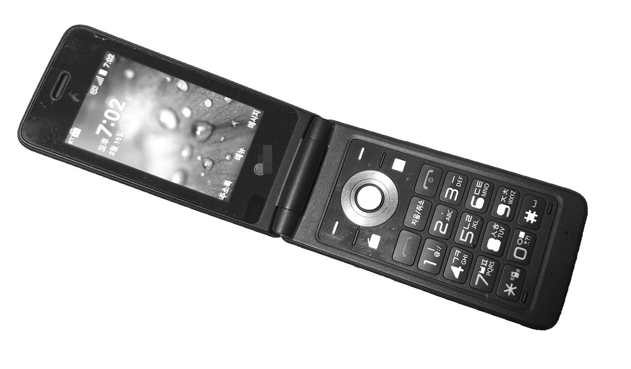 엄마의 오래된 휴대폰  엄마의 휴대폰 뒷면에는 주소종이가 붙여져 있다.