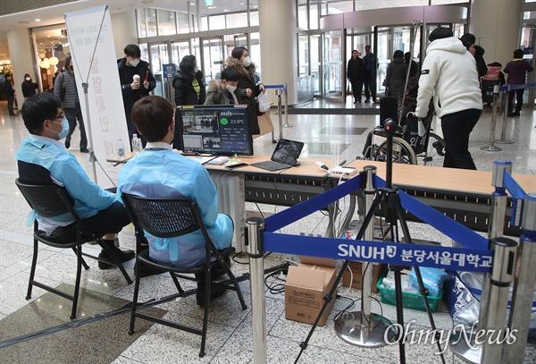 18일 경기도 성남 분당서울대병원에서 병원 관계자가 코로나19(신종 코로나바이러스 감염증) 예방을 위해 내원객들의 발열을 체크하고 있다.