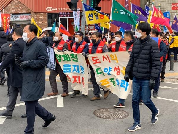 """""""도시의 다양성을 존중하라""""라는 구호가 새겨진 현수막을 들고 행진하는 상공인과 시민들."""