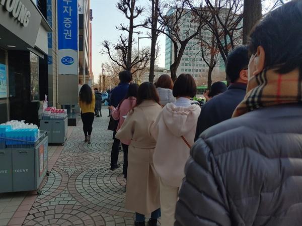 24일 오전 서울 영등포구 여의도 인근 상점에 마스크를 사려는 사람들이 길게 줄을 서있다.
