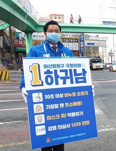 더불어민주당 하귀남 예비후보(마산회원)가 코로나19 예방수칙을 담은 손팻말을 들고 서 있다.