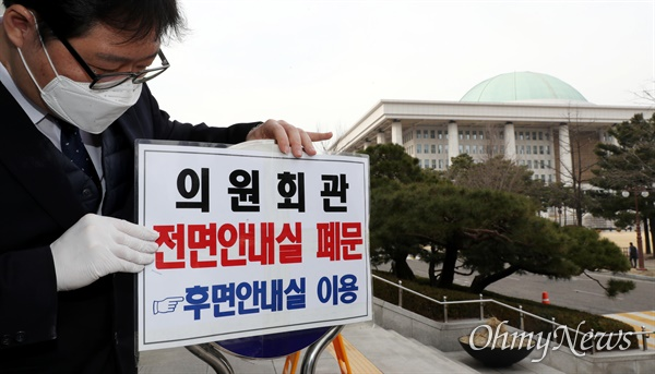 국회도 '코로나19' 비상 '코로나19' 확진자가 지난 19일 국회의원회관에서 한국사학법인연합회 등 교육단체가 주최한 행사에 참석한 것으로 알려진 가운데, 24일 오후 국회 직원들이 의원회관 전면안내실 폐문을 알리는 표지판을 설치하고 있다.