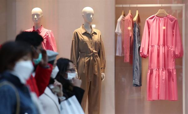 11일 오후 서울 명동 의류매장 쇼윈도의 진열된 봄옷 앞으로 마스크를 쓴 시민과 관광객들이 오가고 있다.