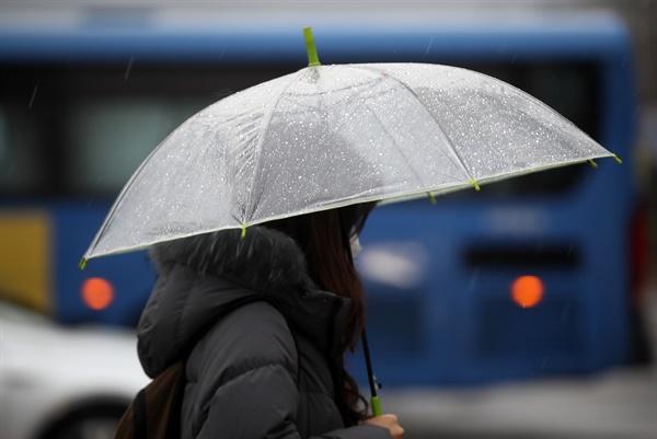 전국이 흐리고 비가 내린 25일 오전 신종 코로나바이러스 감염증(코로나19) 예방 등을 위해 마스크를 쓴 한 시민이 우산을 쓰고 서울 광화문 사거리를 지나고 있다.