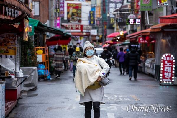 25일 오후 서울 영등포구 대림차이나타운에서 한 시민들이 마스크를 착용하고 아이를 안고 있다.