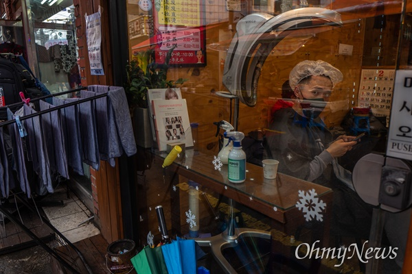 25일 오후 서울 영등포구 대림차이나타운에서 한 손님이 마스크를 쓰고 파마를 하고 있다.