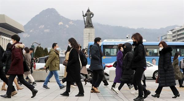 24일 서울 광화문역 사거리 횡단보도에서 시민들이 코로나 19 예방 등의 이유로 마스크를 착용하고 출근하고 있다.