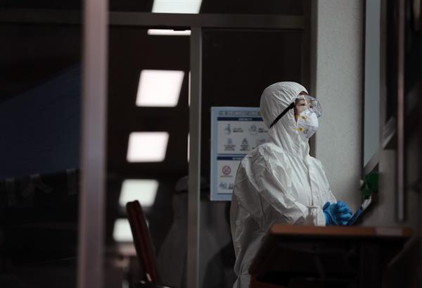 26일 오전 부산 동래구보건소 선별진료소에서 보건소 관계자가 코로나19 의심 환자가 잠시 없는 사이 창밖을 바라보며 두 손을 모으고 있다.