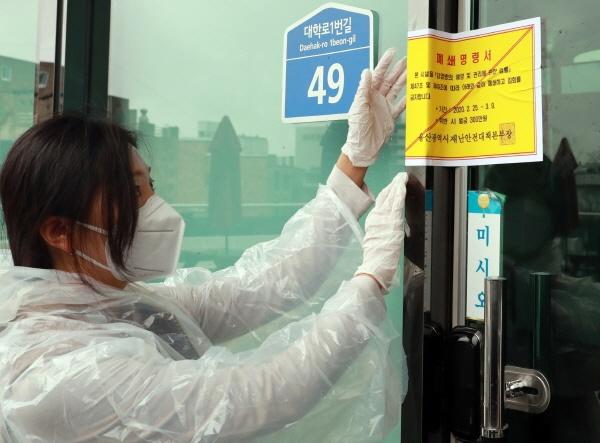 울산시는  코로나19 지역사회 감염을 사전에 차단하기 위해 관내 신천지 교회시설 20개소에 대해 일시적 폐쇄조치 명령을 했다. 25일 울산시 관계자들이 남구 무거동 신천지교회 출입문에 폐쇄명령서를 붙이고 있다.