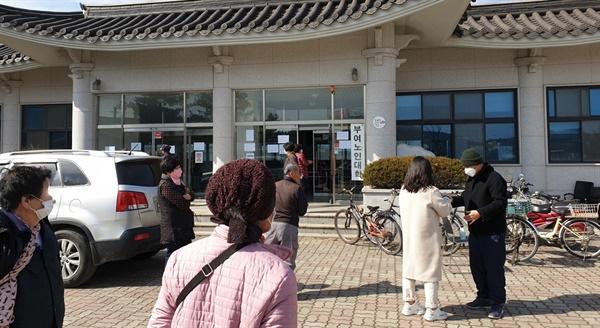 어르신들이 부여군 효공원 소재 부여노인대학(경로식당) 입구에서 체온검사를 받고 있다.