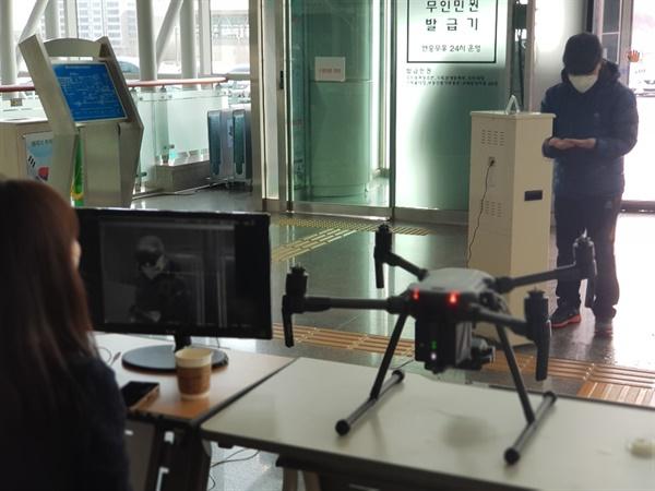 용인시청 출입구에서 드론 열화상카메라를 이용해 출입자들의 증상을 확인하고 있는 용인시 직원 모습