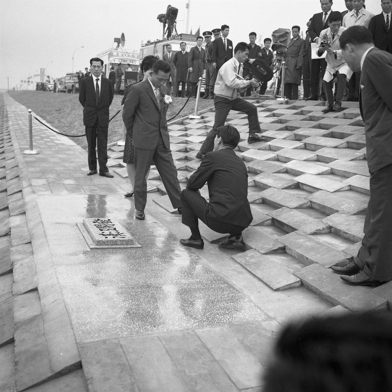 1968년 6월 1일 여의도 윤중제 준공식 여의도를 둘러싼 제방, '윤중제' 준공식에 참석한 박정희 대통령 내외. 제방에 '한강개발'(漢江開發)이라는 표석이 새겨져 있다. 박정희 부부 앞에 앉아 설명하고 있는 사람은 김현옥 서울시장이다. 김현옥은 서울시장 시절 여의도와 한강 개발을 주도했다.