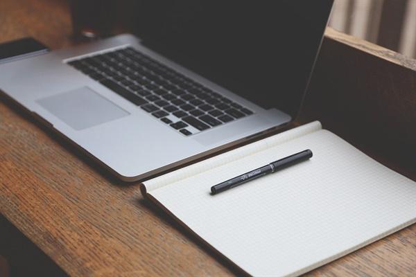 모니터가 꺼진 노트북과 공책, 펜