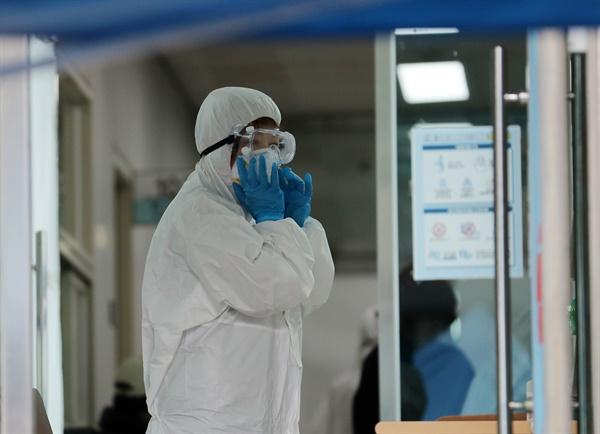 26일 오전 부산 동래구보건소 선별진료소에서 보건소 관계자가 보호장비를 고쳐쓰고 있다.