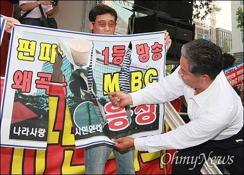 국민행동본부와 뉴라이트전국연합회원들이 2008년 6월 20일 오후 서울 여의도 MBC 본사 앞에서 '광우병선동방송 MBC 규탄' 집회에서 광우병 조작 보도하는 MBC 규탄의 현수막을 찢는 퍼포먼스를 하고 있다.