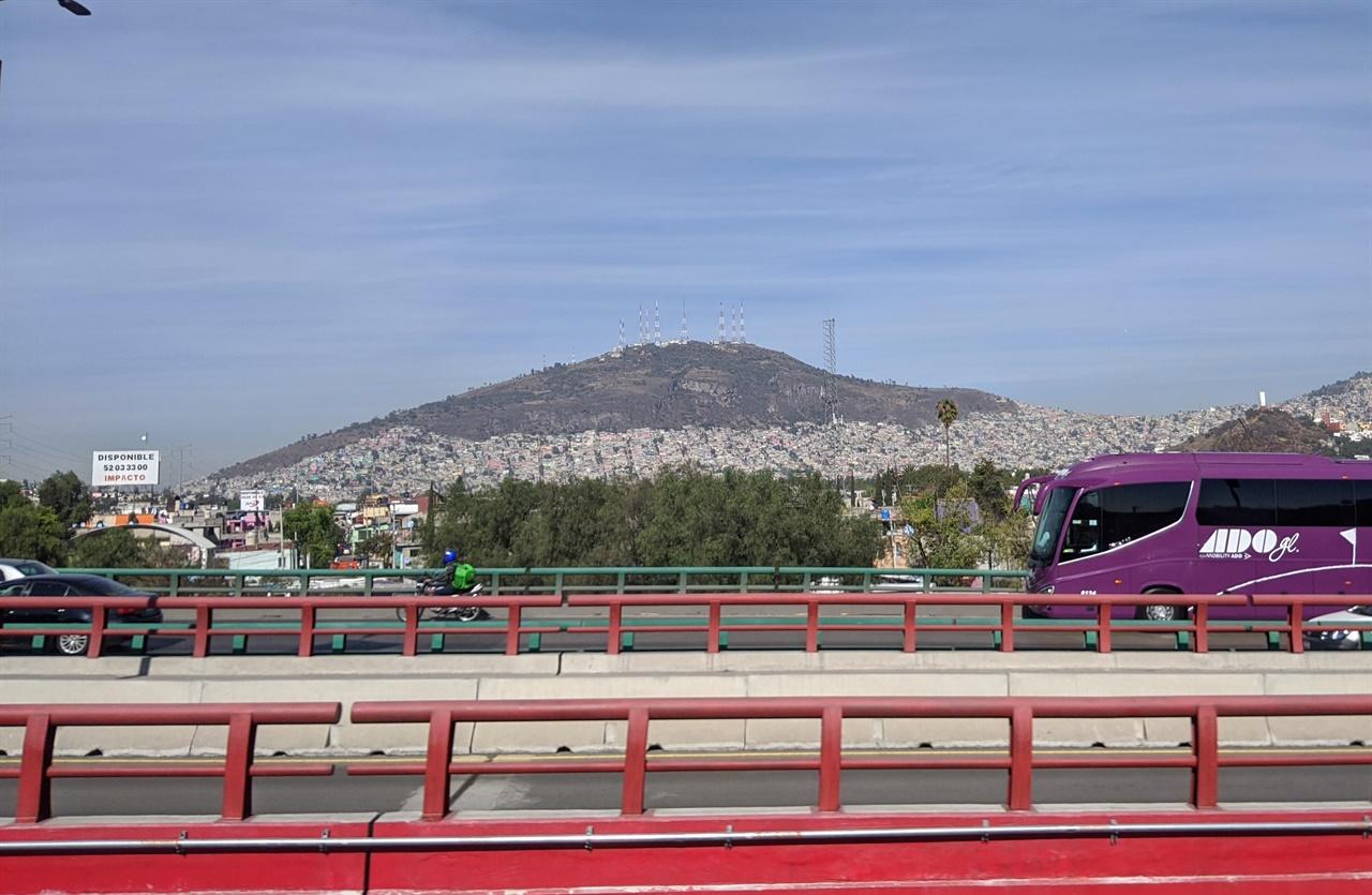 멕시코시티의 외곽 모습 버스에서 촬영한 모습. 산등성이 회색으로 보이는 것이 옥상에 물탱크와 가스통을 이고 있는 집들이다. 70년대 서울의 모습이 떠오른다.