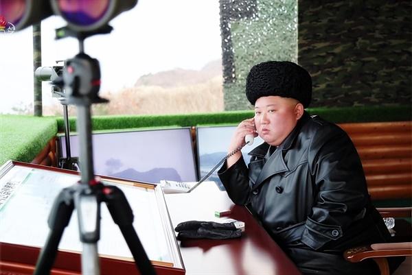 북한 군 합동타격훈련을 참관한 김정은 북한 국무위원장이 실내 감시소에서 누군가와 통화하는 모습을 조선중앙TV가 지난 2월 29일 보도했다. 김 위원장은 마스크를 쓰지 않은 모습이며, 책상에도 담배와 장갑만 보인다.