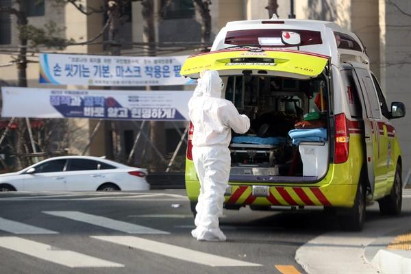 (자료사진)지난 5일 오전 대구시 북구 칠성동에서 119 구급대원들이 코로나19 환자를 병원으로 이송하고 있다.