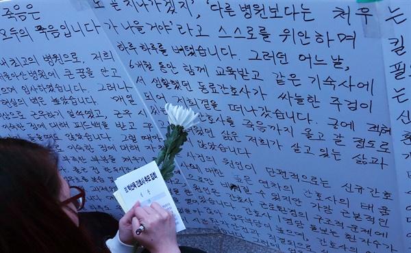 2019년 3월 3일 저녁 서울 광화문역 인근에서 간호사연대NBT 주최로 열린 '고 박선욱 간호사 추모집회'에서 한 참가자가 박 간호사 동료들이 쓴 글을 앞에서 메모하고 있다.