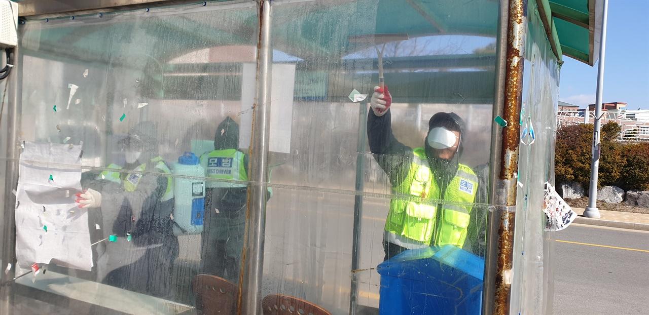 회원이 버스 승강장 내부를 닦아내고 있다.