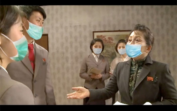 김정화의 연기지도  <민주조선>이 지난달 29일 의료용 마스크를 착용한 북한 여배우 김정화(오른쪽)가 평양연극영화대학 학생들에게 연기 지도를 하는 사진을 게재했다. 북한 전문 매체인 <NK뉴스>는 6일 북한이 포토샵으로 마스크를 어색하게 합성했다고 봤다.