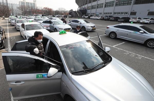지난 4일 오전 경기도 수원시 장안구 수원종합운동장에서 수원개인택시조합 관계자들이 신종 코로나바이러스 감염증(코로나19) 예방을 위해 택시 소독을 하고 있다.