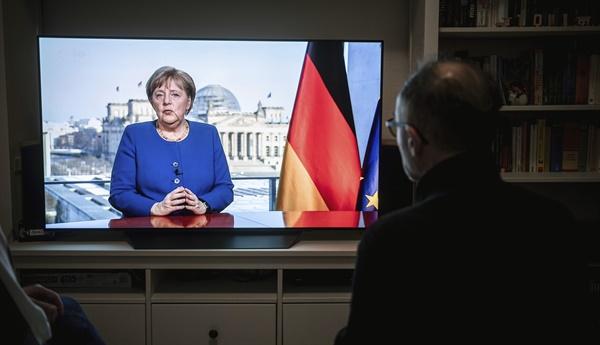 메르켈 총리 대국민 연설 듣는 독일 사람들 독일 오버하우젠의 한 주택 거실에서 18일(현지시간) 사람들이 TV를 통해 신종 코로나바이러스 감염증(코로나19) 확산 사태와 관련한 앙겔라 메르켈 총리의 대국민 연설을 듣고 있다.
