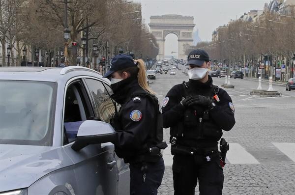 이동금지령 위반 단속하는 파리 경찰 프랑스 정부가 신종 코로나바이러스 감염증(코로나19) 확산을 막기 위해 전국에 이동금지령을 내린 가운데 마스크를 쓴 경찰관들이 17일(현지시간) 파리의 샹젤리제 거리에서 차량 운전자들의 이동 증명서를 확인하고 있다.