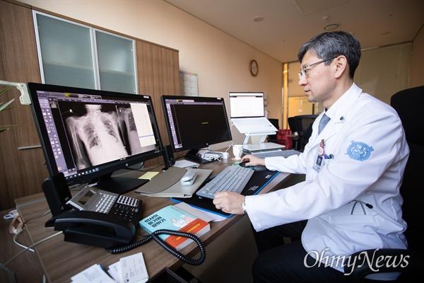 김홍빈 분당서울대병원 감염내과 교수가 코로나 9 감염 환자의 폐 상태 엑스레이 화면을 설명하고 있다.