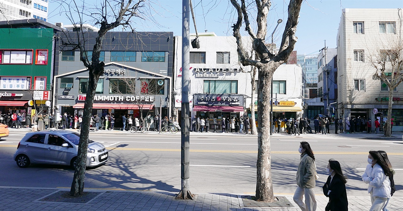 마스크를 쓰고 거리를 지나는 시민들 뒤편으로 마스크를 사기 위한 줄이 길다. 서울 성수동에 마스크를 통해 우리는 각자 어떤 이야기를 해야하는가? 언론은, 정책디렉터는 어떤 의제를 떠올리고, 방향을 잡아야 하는가.