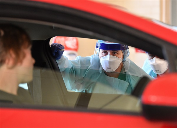 호주 코로나19 드라이브스루 선별진료소 사우스오스트레일리아병원 직원이 지난 20일 호주 애들레이드에 있는 한 병원에서 코로나19 감염증 검사를 통해 차량탑승진료 검사를 실시하고 있다.