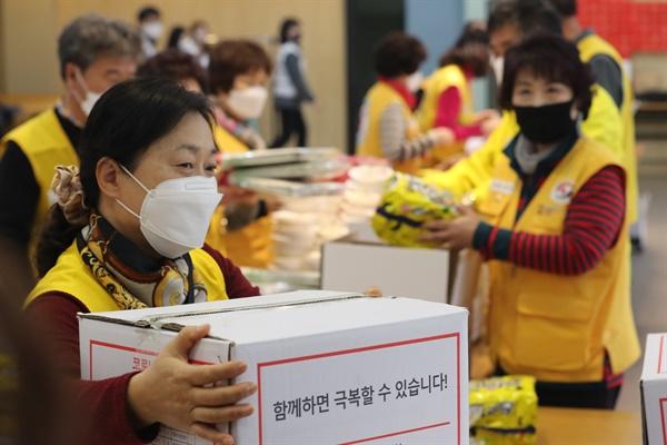 19일 오후 경기 수원시 대한적십자사 경기도지사 강당에서 봉사자들이 재난 취약계층에게 나눠줄 신종 코로나바이러스 감염증(코로나19) 긴급구호세트를 포장하고 있다.