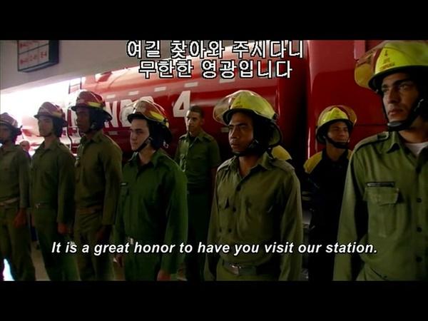 다큐멘터리 <식코>의 한 장면. 쿠바의 소방대원들이 미국 소방대원 등을 환영하고 있다.