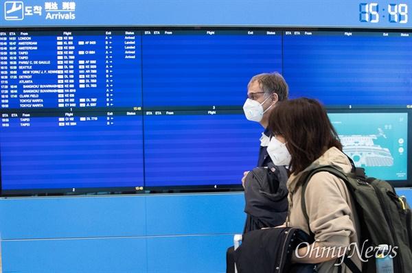 24일 오후 인천국제공항 제2여객터미널로 입국한 외국인 승객들이 경찰의 안내를 받으며 '코로나19' 관련 격리시설로 이동하고 있다. '코로나19'가 세계 각국에서 발생하면서 비행기 운항이 대폭 중단되어 도착을 알리는 전광판이 대부분 비어 있다.