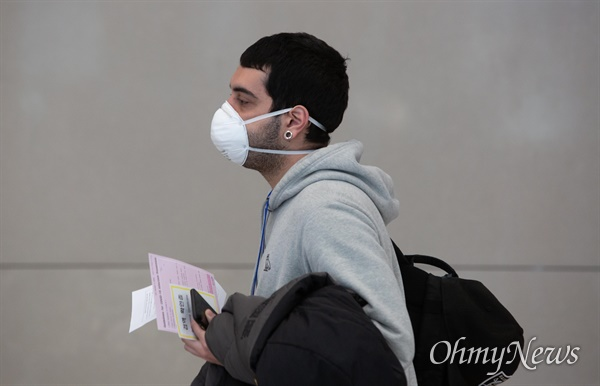 24일 오후 인천국제공항 제2여객터미널로 입국하는 외국인 승객들이 '코로나19' 관련 격리시설로 향하기 위해 대기장소로 이동하고 있다.