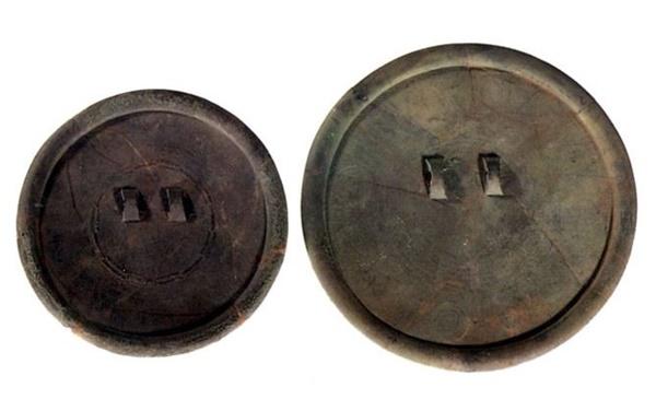 청동 잔무늬거울. 거울 뒷면에 기하학적인 문양과 거울을 매달 때 사용하는 두 개의 뉴가 달려 있다. 국보 제143-6호