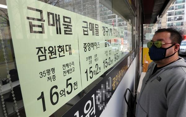지난 24일 서울 서초구 한 공인중개사 앞에서 시민이 급매 게시물을 살펴보고 있다.