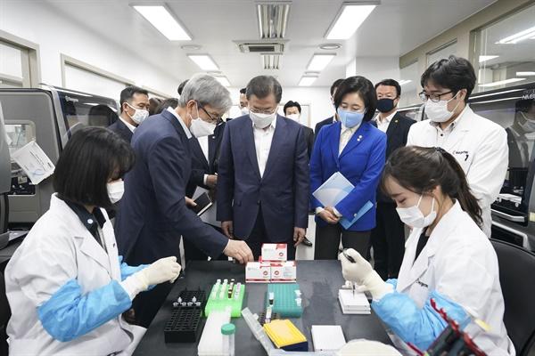 문재인 대통령이 25일 코로나19 진단시약 긴급사용 승인 기업 중 하나인 송파구 씨젠에서 연구시설을 둘러보고 있다.